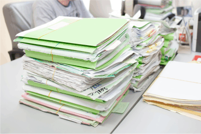 Files  in cardboard folders stacked on a desk waiting for collection and bulk scanning by PaperMountains document bulk document scanning service bureau.